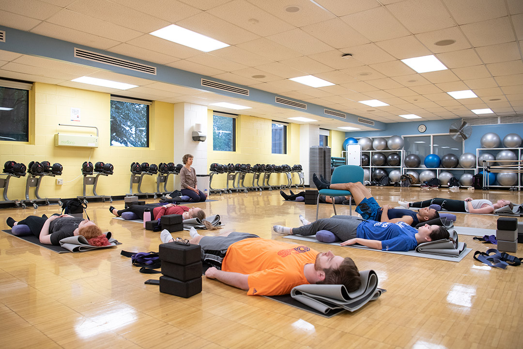 Students lay on gym floor in yoga poses.