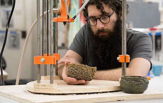 Student uses 3D ceramic printer.