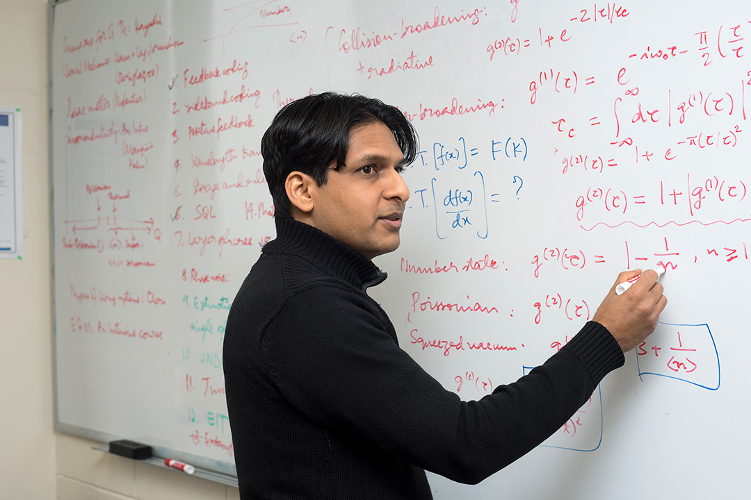 Mishkat Bhattacharya standing in front of white board and writing out equations.