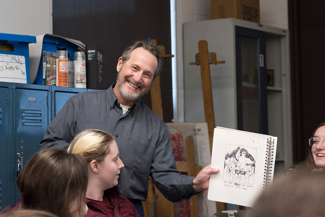 Leigh Rubin holds up a sketch and smiles at the camera as students look on.