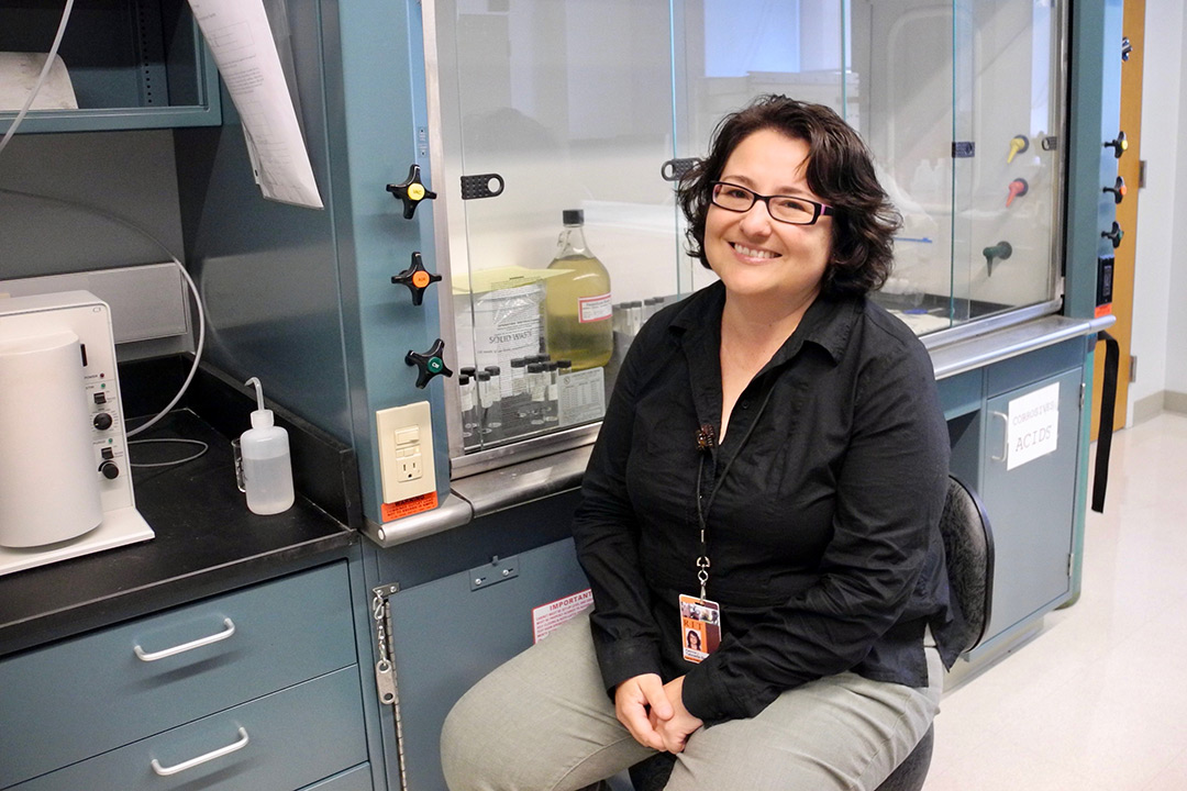 Patricia Taboada-Serrano poses for a photo in front of a fume hood in a lab.