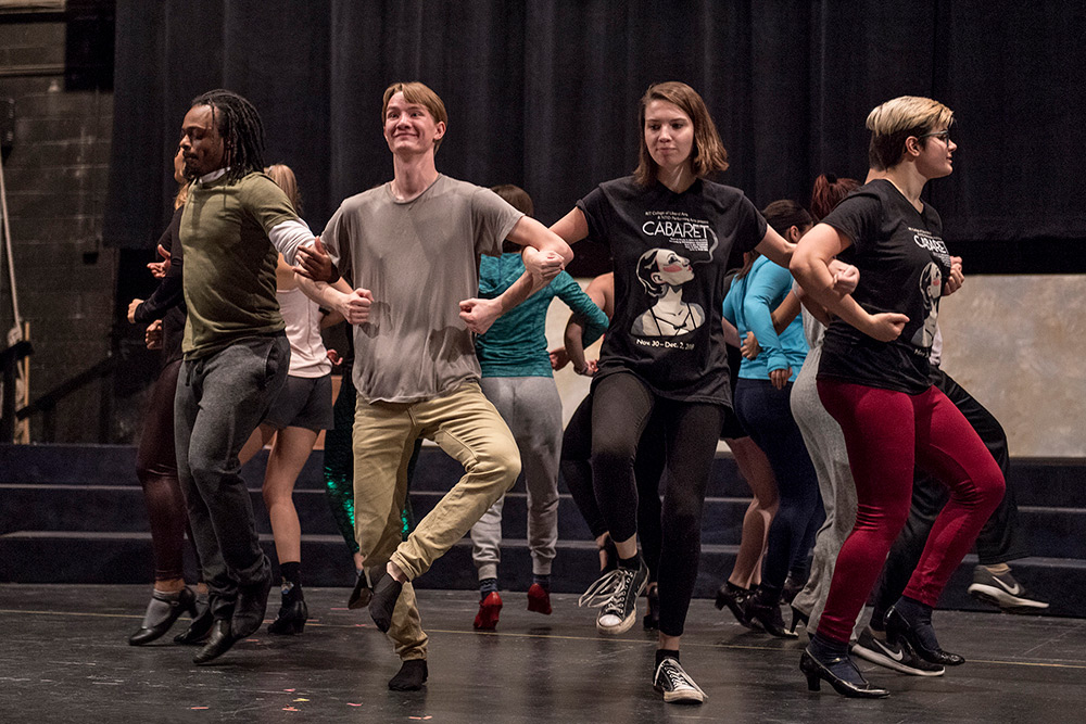 Members of the cast practice a group dance, their arms linked together as they move around in a circle.