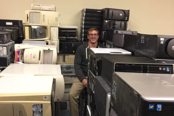 Josh Geise sits among stacks of computers, his head poking out from the top of a stack.