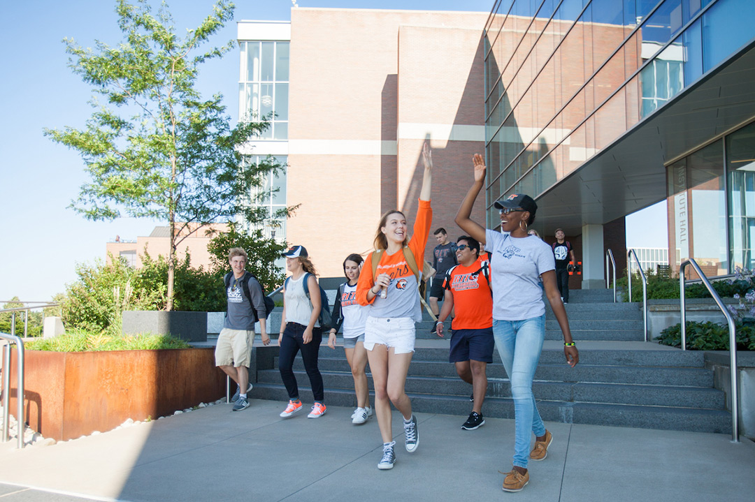A group of students walking together on campus, two girls giving each other a high five.