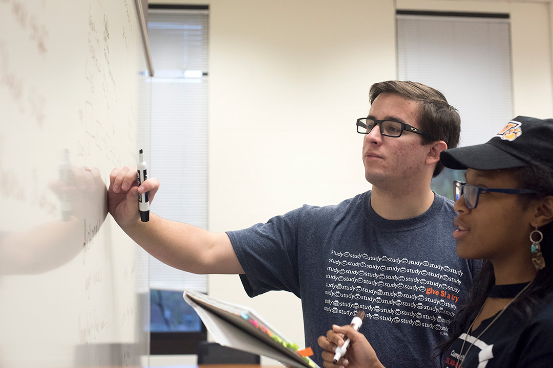 Students standing in front of a white board while they work with different formulas.