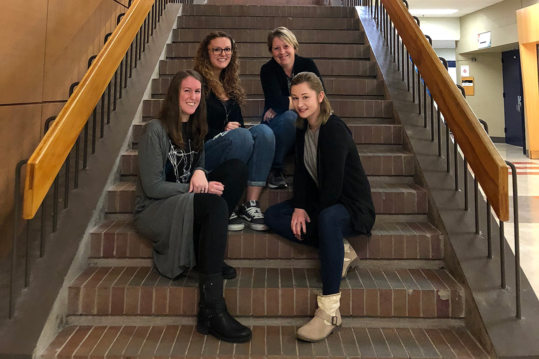 The four students who collaborated on the art space design pose for a photo on a brick staircase.