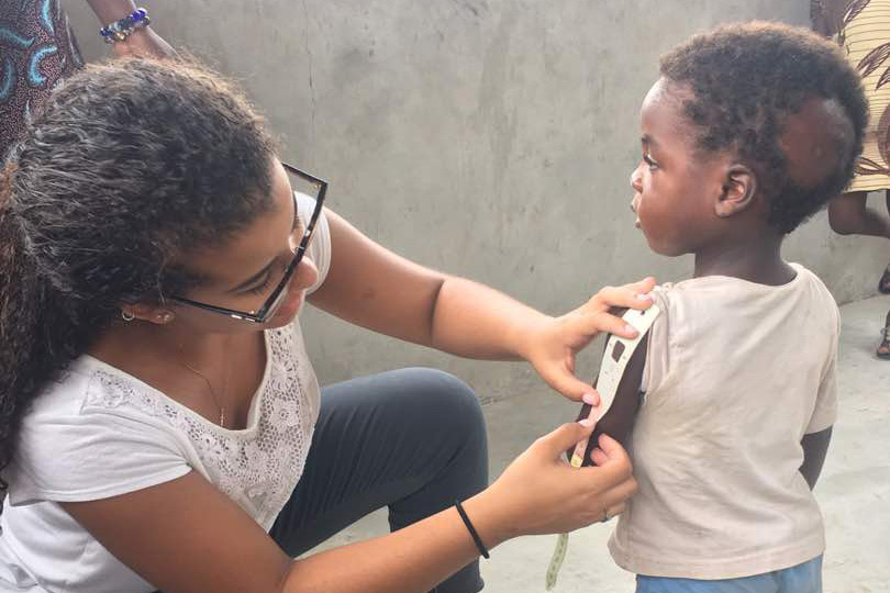 Woman measures arm of child with strip to determine anemia.