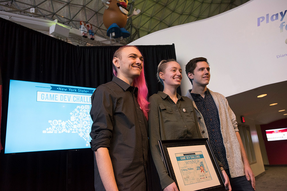 Three students holding the Game Dev Challenge award certificate.
