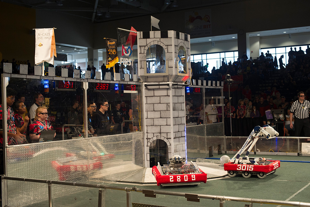Two teams look on as their robots perform for the competition.