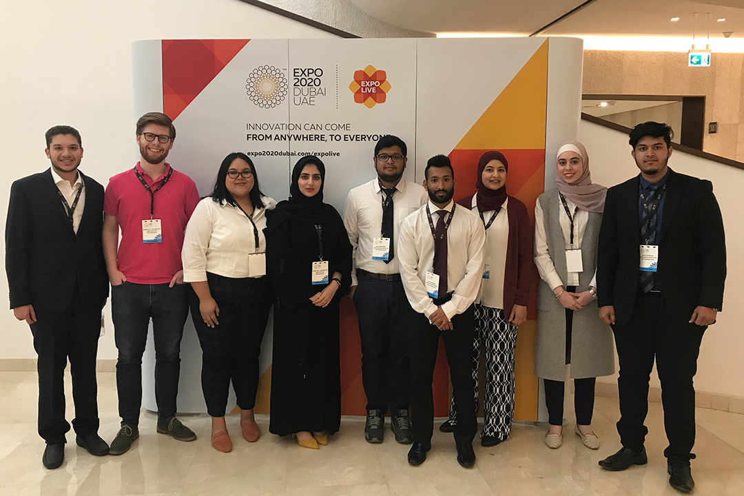 A group of RIT Dubai mechanical engineering students pose in front of a poster for the Expo.