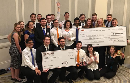 The teams who attended the Associated Schools of Construction annual design competition pose for a photo with their large checks and other awards.