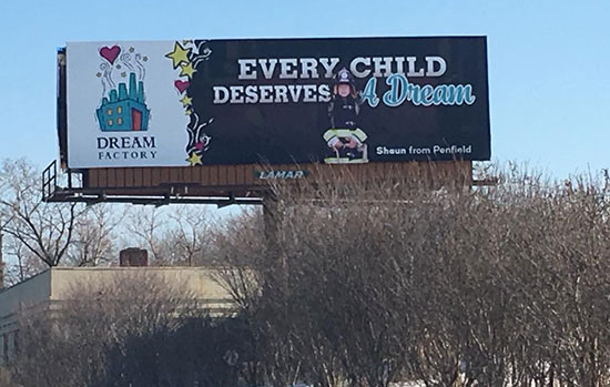 "A photo of the billboard designed by the advertising and promotion management class. It reads, ""Every Child Deserves A Dream"" in large text on the right, and on the left there is a illustrated photo of a small factory with the words ""Dream Factory"" written below."