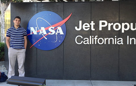 Erez Binyamin poses for a photo next to a large NASA sign outside of the Jet Propulsion Center.