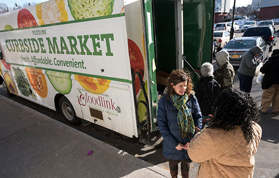 A photo of Foodlink's curbside market truck. People stand around the truck talking.