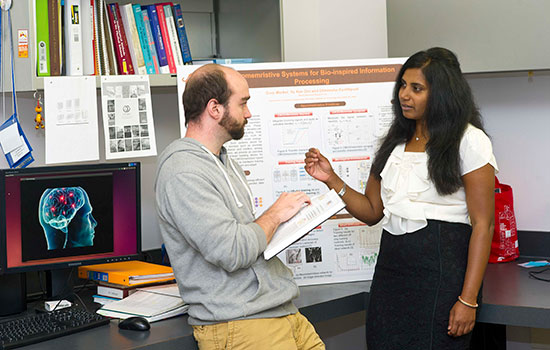 Dhireesha Kudithipudi converses with a student in her office, a research poster hanging behind them.