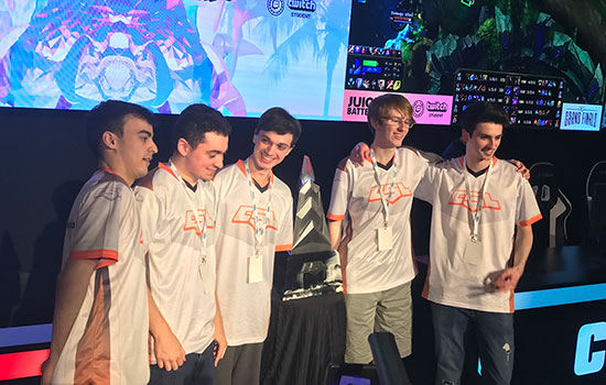 The winning RIT Dota 2 team poses for a photo with their trophy.