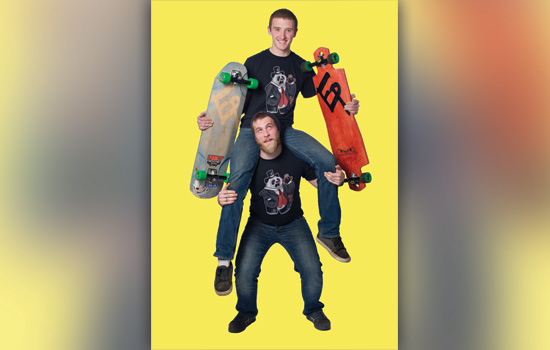Two people posing with skateboards