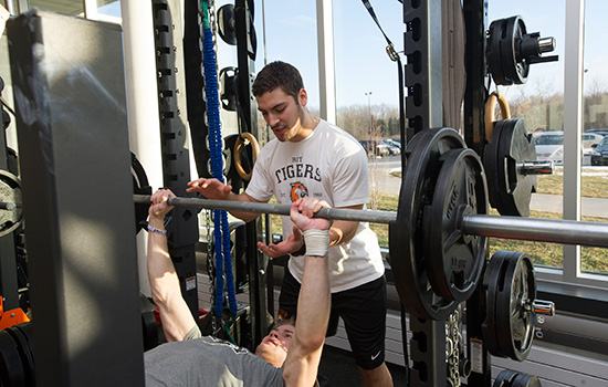 An exercise science student spots another student as he does a bench press.