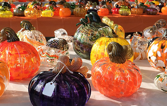 'A patch of glass pumpkins on a table.'