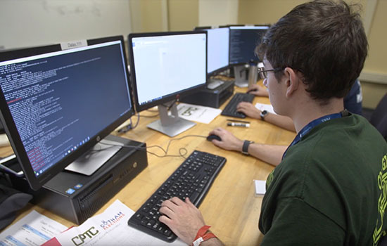 A student sits in front of a computer and writes out code, which is visible on the desktop screen.