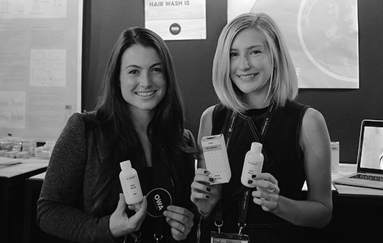 Lindsay Reardon and Kailey Bradt smile for a photo, holding up the products they created.