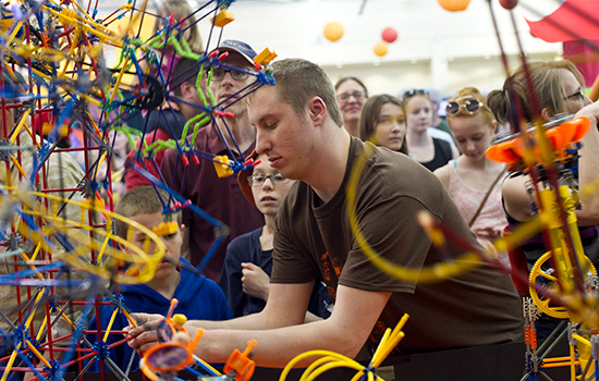 A student at Imagine RIT adjusts the toy-model of a theme park while children and their parents look on behind him.