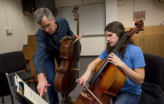 Professor Haritatos instructs a student on how to play the cello, pointing at the sheet music as the student plays the song.