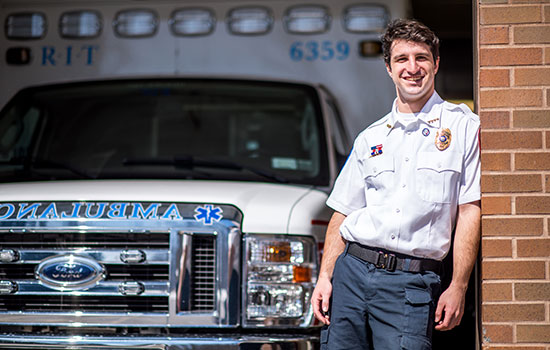 Oren Cohn poses for a photo in his RIT Ambulance uniform in front of one of the ambulance vehicles.