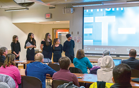"The Jet-2k team stands at the front of a room and shows students and potential ""investors"" a video about their packaging design."