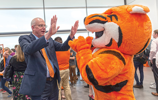 President Munson high-fives tiger mascot.