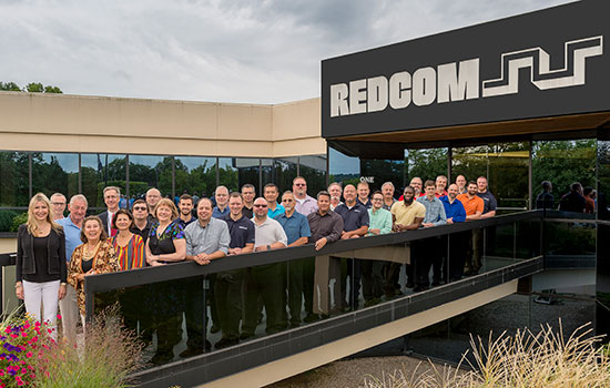 Members of REDCOM and RIT pose for a group photo outside the REDCOM office.