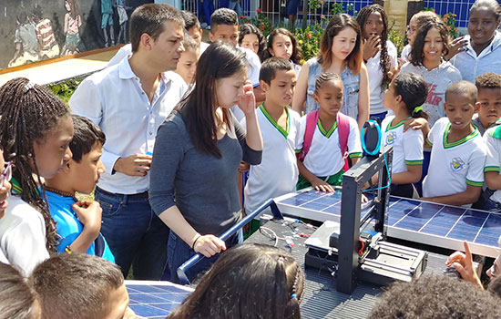 Team members demonstrate their new 3D printer and young students crowd around them to look and see the machine function.