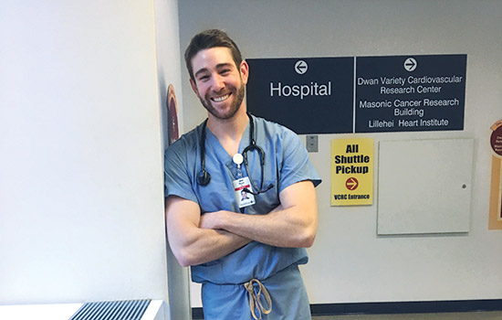 Ryan Buckley poses for a photo in his scrubs at a medical center.