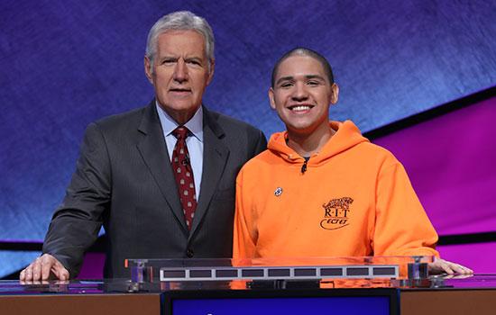 Sheldon Lewis smiles next to Alex Trebek, wearing a bright orange RIT sweatshirt.