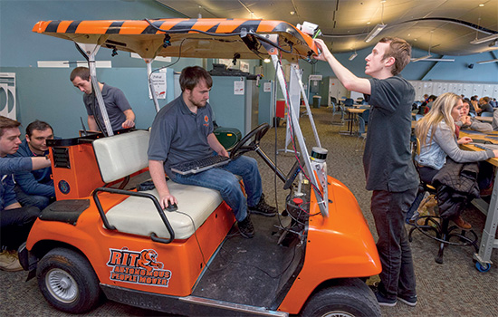 A group of students put the finishing touches on the Autonomous People Mover and check to make sure everything is placed and functioning properly.