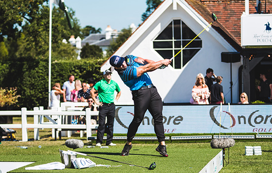 Ryan Steenberg hitting a golf ball at a competition, his arm and club still extended in the air.