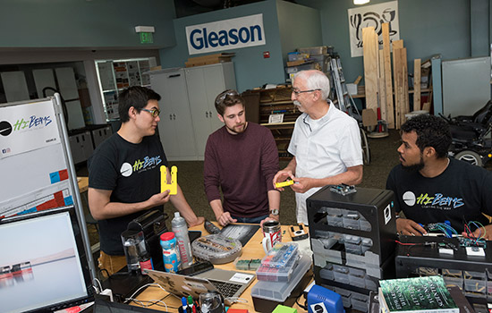 Three students and their mentor stand at a work bench and discuss their next steps in the project.