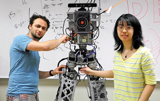 Two members of the TigetBot team pose with their robot.