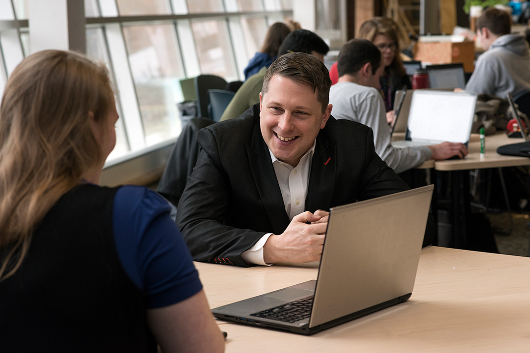Michael Oshetski sits with a student in front of a laptop smiling.