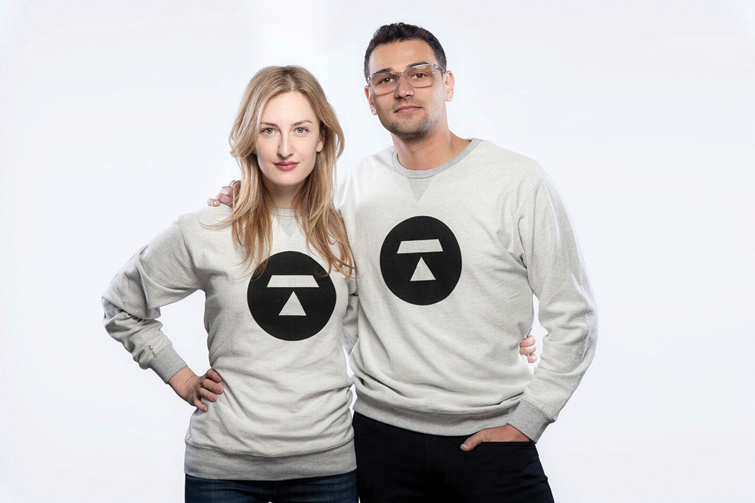 Melanie and Steve Shapiro pose for a photo wearing sweatshirts with the logo of their newest company, Token, on the front of it.