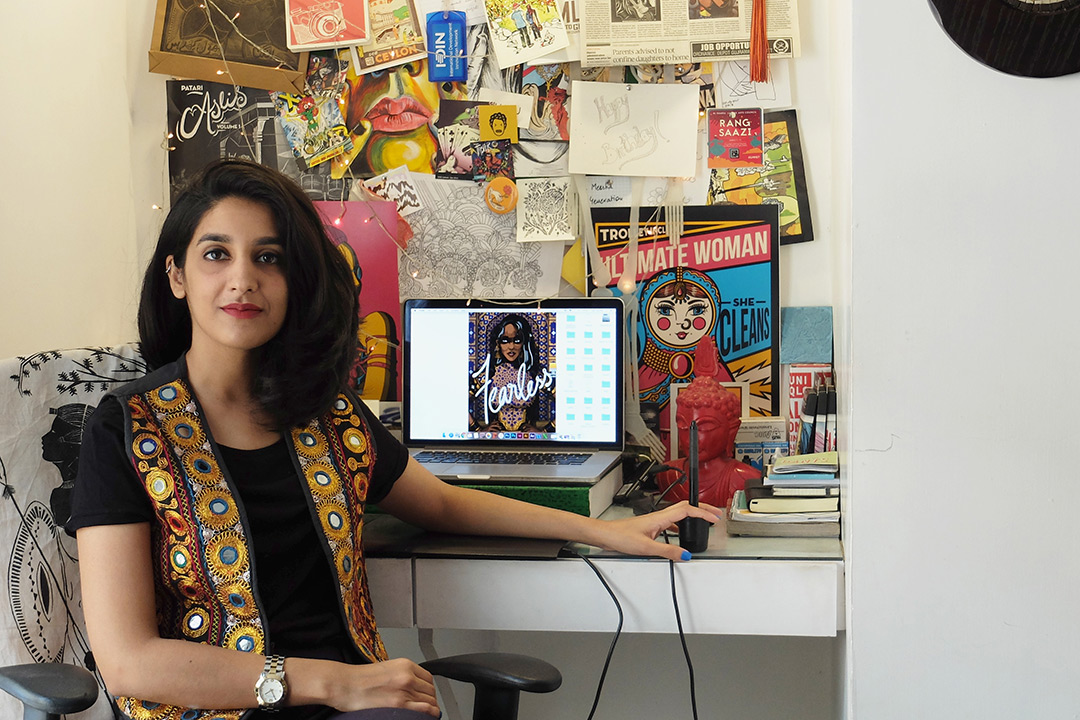 Shehzil Malik sits at her desk and poses for a photo. Her desk and wall are covered in colorful artwork.