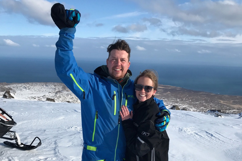 Brynjar and Brianna pose for a photo shortly after getting engaged. Brynjar holds his fist up in their air, seemingly in triumph.