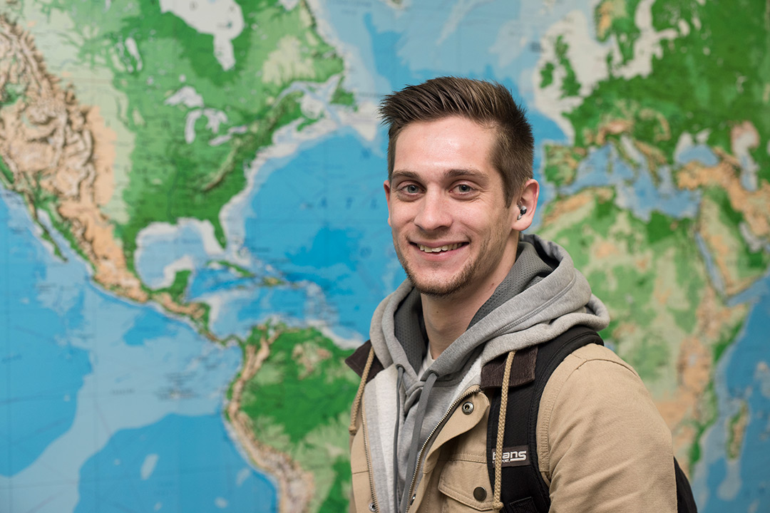 Connor Draughn poses for a photo and smiles in front of a large world map.