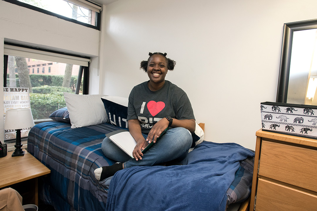 Shantinique Cowans sits on her bed in her dorm room, smiling and holding a book open in her lap.