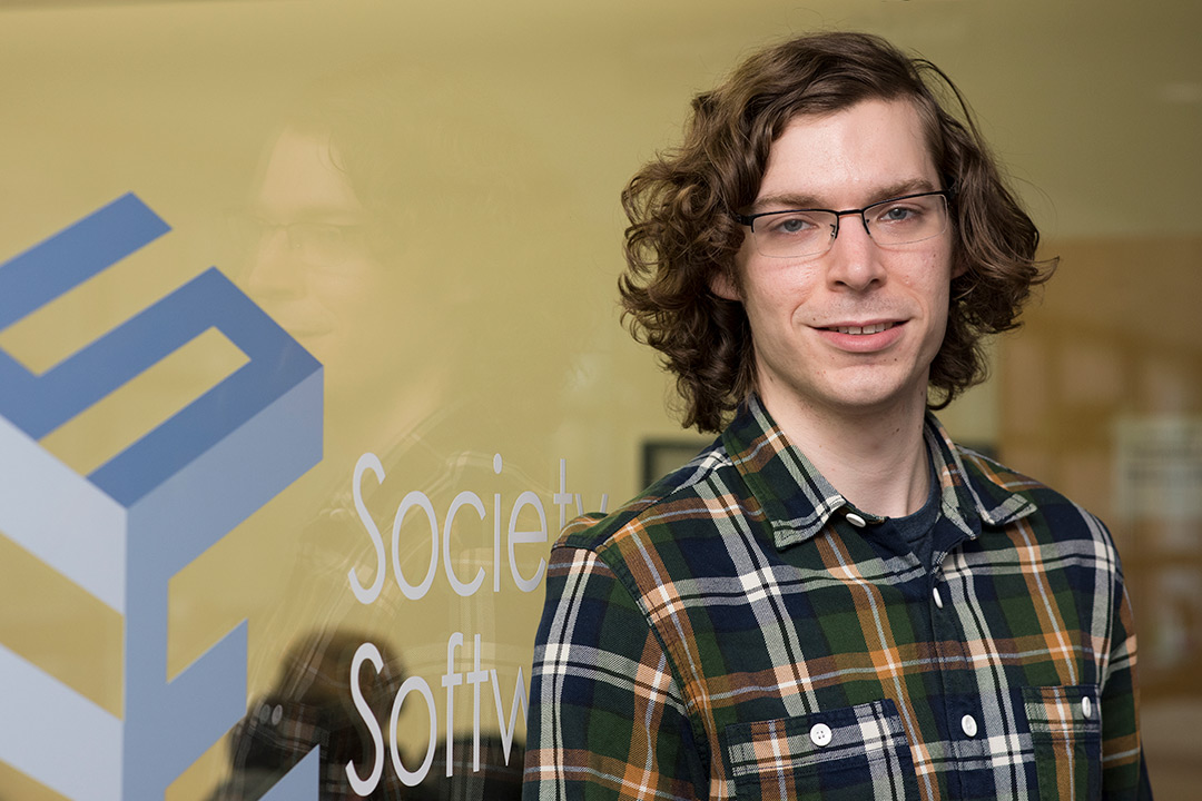 "A portrait photo of Robert McLaughlin standing in front of a glass wall reading ""society of software engineers."""