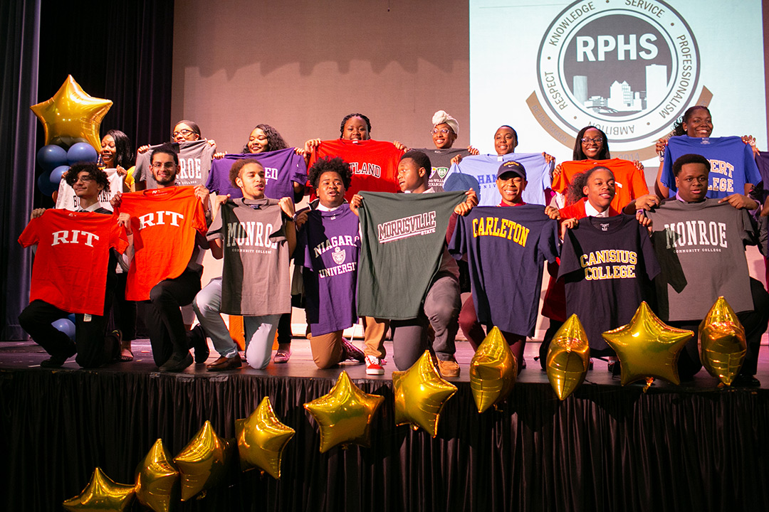 A group of graduating students from Rochester Prep High School stand on a stage and hold up t-shirts from the colleges they have been accepted into for the fall.