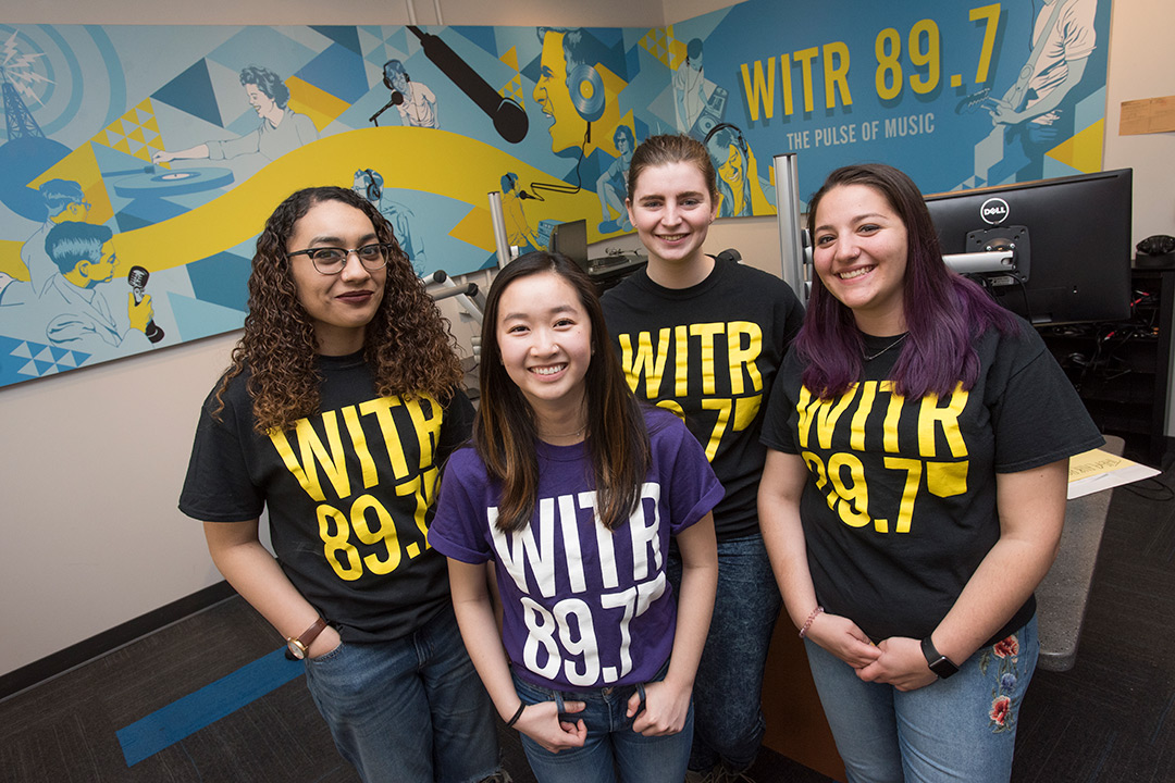 The four women e-board members stand together in the stations broadcasting room.