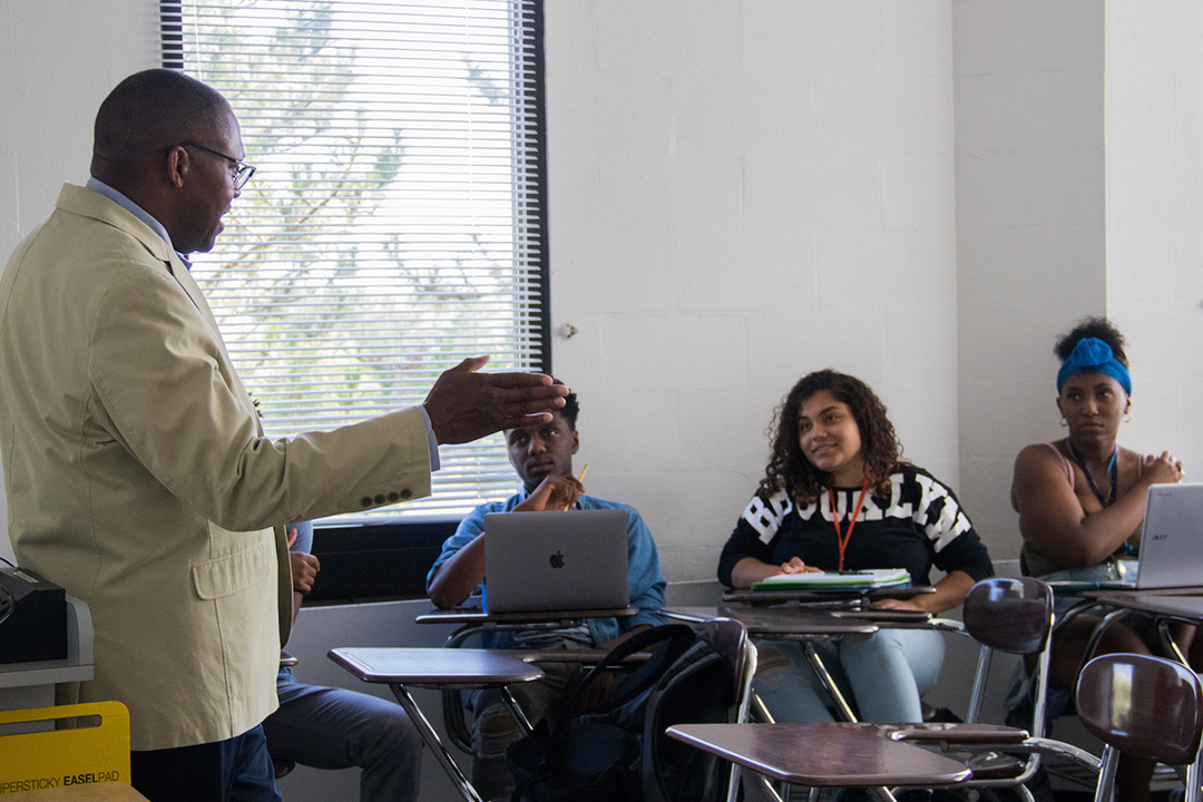 Keith Jenkins stands at the front of a room and speaks to three students who sit at desks with their laptops and paper for notes.