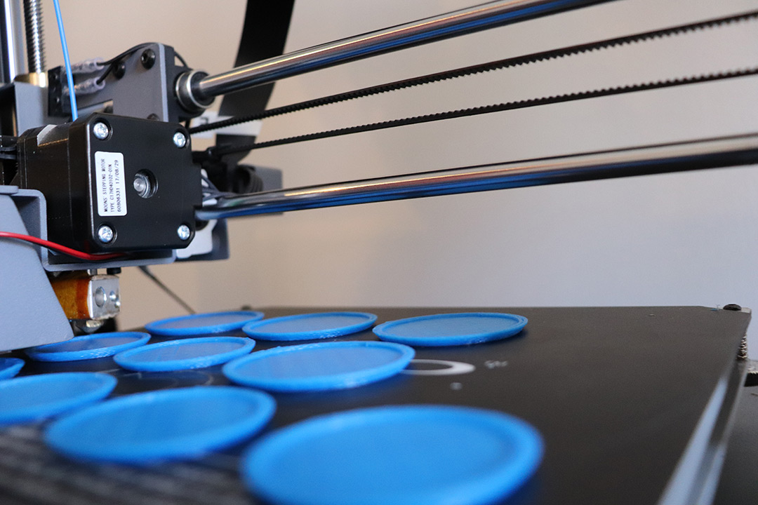 A 3D printer at work, printing 10 blue, flat, circular objects.