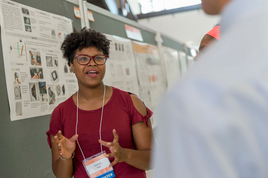 Cianna Dresden Hall excitedly explains her research to onlookers, talking with her hands and smiling as she speaks.